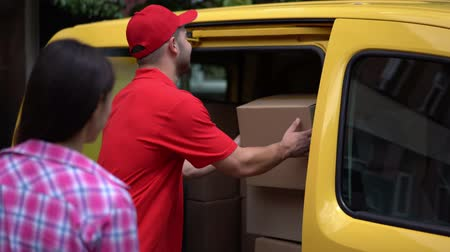 выполнять : Cheerful Delivery Guy In Red Shirt And Baseball Cap Gives Ordered Package To The Girl. Smiling Guy From Delivery Service Takes Out The Box From The Yellow Car To The Customer