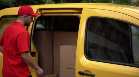 kutu : Man In Red Shirt And Baseball Cap Opens Slide Van Door To Take Out The Cartoon Box. Happy Guy From Delivery Service Is Holding A Parcel Before Giving It To The Customer