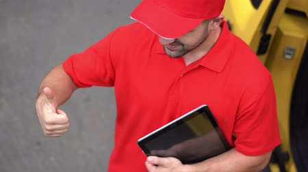 polegar : Delivery Man In Red Shirt And Baseball Cap Shows Thumbs Up Gesture While Holding A Modern Tablet. View From Above On Delivery Guy Showinп Thumbs Up