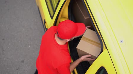recipient : Handsome Guy In Red Uniforn Takes Out A Cardbox From Yellow Van And Gives It To A Woman. Look From Above On The Delivery Man Working With Orders Stock Footage