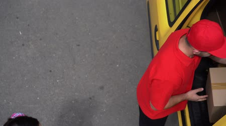 recipient : Brunette Girl Take Her Ordered Cardbox From The Delivery Guy In Red Uniform. View From The Car Roof On Guy From The Delivery Service Taking Out A Package From The Yellow Van.