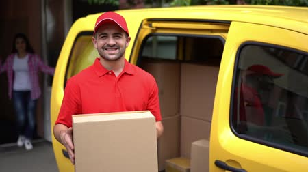 クーリエ : Handsome Delivery Man In Red Uniform Stands Near Yellown Truck While Holding Ordered Parcel. Smiling Guy From Post Service Holds A Cardbox Standing Near Yellow Car.