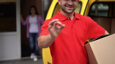 caixa de correio : Joyful Guy In Red Uniform From Delivery Service Shows Ok Sign. Smiling Young Man From Shipment Service Holds Carton Box And Shows Ok Gesture. Stock Footage