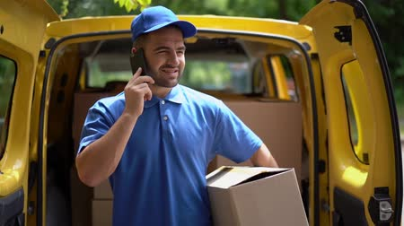 postpakketje : Handsome Guy In Blue Shirt And Baseball Cap Talks On The Phone While Holding A Parcel Near Open Yellow Truck. Concentrated Delivery Man Holds A Parcel And Talks On The Mobile Phone With A Customer,
