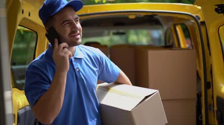курьер : Attractive Delivery Man Is Talking On The Phone And Walking While Holding A Package. Smiling Guy In Blue Uniform Talks On Mobile Phone While Walking With A Package In Hands And Waiting For A Customer,