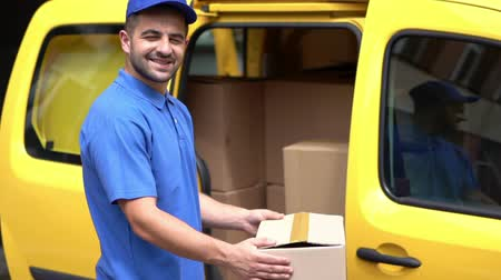 выполнять : Cheerful Courier Take Out The Package From Yellow Van. Handsome Delivery Guy In Blue Signs Is Getting Medium Size Package Out Of Postal Truck.