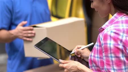 job transfer : Courier In Blue Uniform Holds A Carton Box Package While Young Woman Signs Delivery Documents On Tablet, Stock Footage