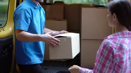 занятость : Beautiful Woman Receives Her Ordered Package From Delivery Guy In Blue Uniform, Who Takes It Out From His Yellow Van. Shipment Concept Стоковые видеозаписи