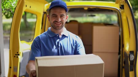 почтальон : Proud Young Delivery Man In Blue Uniform Is Holding A Box While Standing At The Doorstep To Deliver The Order. Cheerful Courier Stands In Front Of The Open Doors Of A Yellow Van And Gives An Ordered Package