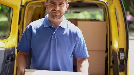 trabalhar fora : Handsome Postman Take The Caron Box Out Of Delivery Truck, Walks Towards Holding A Parcel In His Arms And Expressively Shows The Ok Sign