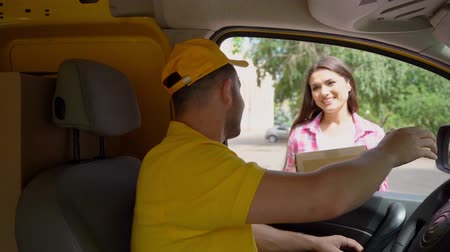 caixa de correio : Handsome Courier In Yellow Outfit Delivers Caron Box To Beautiful Woman While Sitting In A Van. Shipment And Delivery Concept, Vídeos