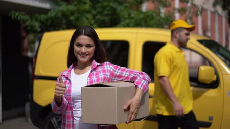 polegar : Cheerful Young Woman In Casual Cloth Shows The Ok Sign And Holds A Big Carton Package. The Driver In Yellow Uniform Closes The Door Of A Yellow Delivery Van Behind The Posing Woman Showing Ok