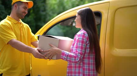 postacı : Smiling Postman Gives Parcel To The Beautiful Woman. Near Yellow Delivery Truck Happy Gril Receive Her Package From The Cheerful Courier