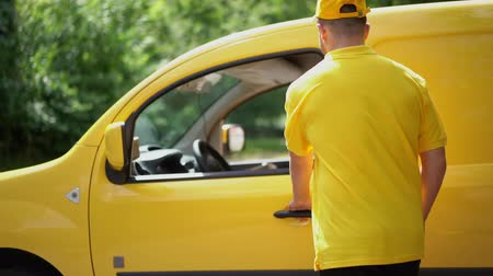 trucks : Attractive Woman Takes Caron Box From Delivery Man In Yellow Uniform. After Giving The Ordered Parcel To Excited Female Client The Courier Returns To His Yellow Van And Sits In Driver Seat Smiling,
