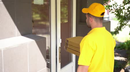 クーリエ : Handsome Pizza Deliverer Rings A Door Bell. Happy Woman Gives Money To The Courier To Pay The Bill And Take From Him The Pizza Boxes. Food Delivery