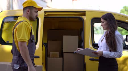 corriere : Concentrated Woman In Business Outfit With Clipboard In Her Hands Explains The Details Of The Shipment To The Courier In Yellow Uniform.