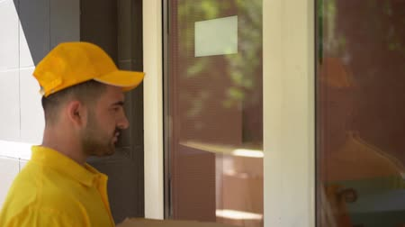 doorway : Delivery Guy In Yellow Outfit Ring A Doorbell To Deliver Food Boxes. Smiling Woman Take The Pizza Boxes And Thanks The Courier By Giving Him Money.