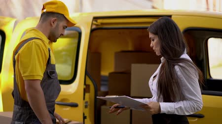 makbuz : Beautiful Woman Gestures And Shows Details To The Delivery Man. Signing Receipt For Delivering Parcel From Male Courier. Shipment Concept