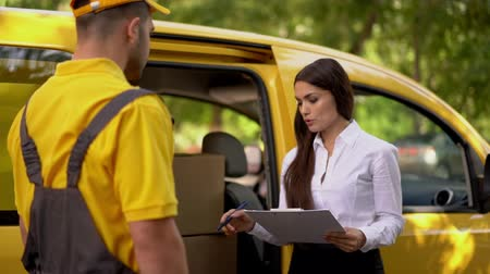 caixa de correio : Young Woman With Tablet And Courier Discuss The Details Of The Delivery Process. Woman Describes The Delivery Man In Yellow Uniform The Shipment Procedure. Stock Footage