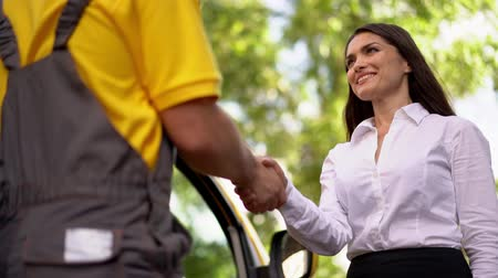 kennismaking : Pretty Girl Shakes Hands With Delivery Man. Delivery Concept. Cooperation