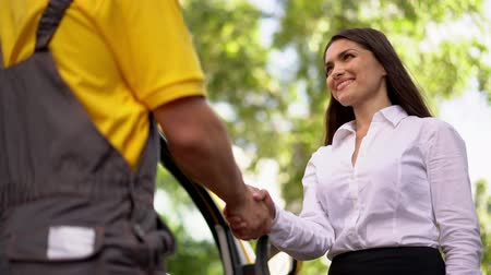 курьер : Smiling Businesswoman Shakes Hands With A Courier In Yellow Uniform. Agreement Concept