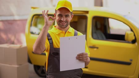 postacı : Portrait Of Handsome Postman Showing An Ok Sign While Holding Delivery Papers. Big Yellow Van In The Background
