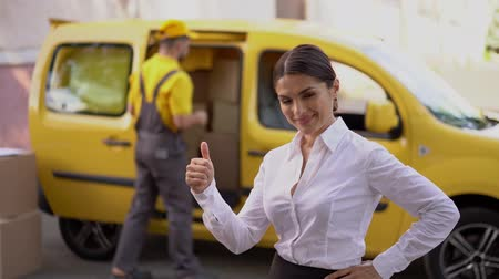polegar : Young Girl In Elegant Cloth Show A Thumb Up Standing Near The Yellow Delivery Van. Courier In Yellow Outfit Walks Past Mail Van While Cheerful Businesswoman Thumbs Up