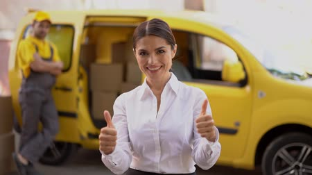 polegar : Attractive Girl Smiles And Shows Two Thumbs Up. Blurred Image Of Yellow Delivery Truck With A Courier Leading Against It.