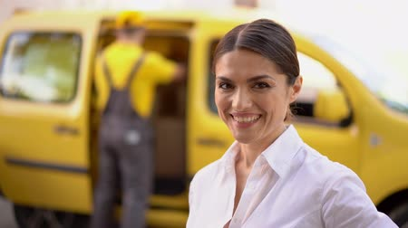 занятость : Close Portrait Of Attractive Brunette Woman Who Shows A Thumb Up While Standing In Front Of The Yellow Delivery Car With A Courier Searching Something In It Стоковые видеозаписи