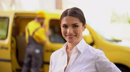 kifejező pozitivitás : Bright Close-Up Shot Of Attractive Woman In Business Outfit Showing Thumb Up. Blurred Image Of Busy Delivery Man Near Yellow Car In The Background