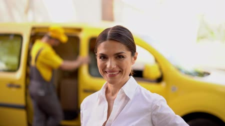 курьер : Happy Female Customer In Business Suit Shows Ok Sing For The Delivery Service. Blurred Image Of Delivery Truck And Courier At The Background.