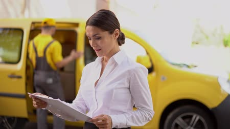 postpakketje : Concentrated Woman In Office Outlook Read From The Clipboard Standing In Front Of A Yellow Delivery Truck. Outdoor.