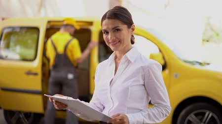 postpakketje : Beautiful Businesswoman Glimpses At Clipboard Before Looking In Camera. Blurred Shot Of The Background Where Busy Delivery Guy Is Moving Boxes Inside A Yellow Van Stockvideo