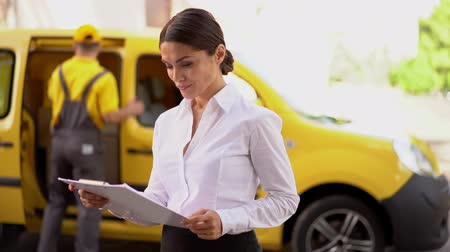 postacı : Stylish Brunette Holds A Clipboard And Checks The Content Of It. Blurred Postman Stands Near His Delivery Truck Behind Pretty Businesswoman With A Tablet. Stok Video
