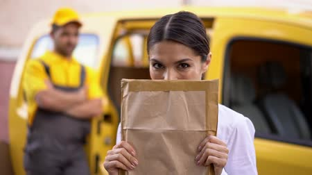 почтальон : Pretty Businesswoman Glimpses Behind Received Parcel To The Camera. Happy Woman Hides Half Of Her Face With Delivered Package. Delivery Concept.