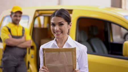 почтальон : Portrait Of Excited Business Woman Holding A Long-Waited Parcel In Front Of Her Face. Blurred Image On Proud Courier Standing Near His Van After Giving Parcel To Smiling Woman. Стоковые видеозаписи