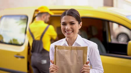 почтальон : Stylish Brunette In Business Outfit Holds A Ordered Package And Smiles At Camera. Delighted Woman Wilth Carton Parcel Is Extremely Happy For Such Quick Delivery, Shipment Concept.
