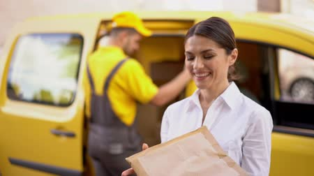 почтальон : Stunning Businesswoman Shows Happiness After Receiving Her Order. Elegant Girl Holds Tight Delivered Parcel And Smiles At Camera. Concentrated Delivery Man Closes The Door Of His Yellow Car After Fulfilling His Order And Giving Parcel To A Woman.