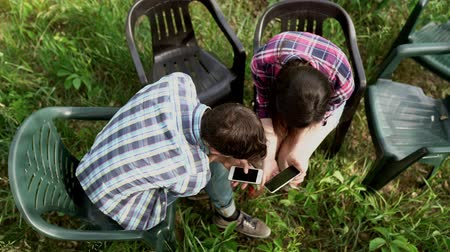 сотовый телефон : Top View Of Two Friends Sharing Photos Between Their Phones From The BBQ Party. Стоковые видеозаписи