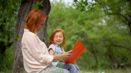 narożnik : Smiling Redhead Girl Sits On Her Lovely Mothers Knees And Point At Camera. Happy Women With Sweet Child Who Is Pointing His Finger To The Camera Sit At The Tree On The Right Corner Of An Image