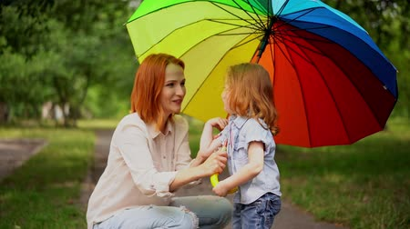 скрывать : Attractive Woman Holds A Coloured Umbrella Over Her Little Redheaded Daughter. Family Of Mother And Child Hide Under Bright Umbrella From The Rain. Стоковые видеозаписи