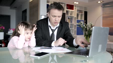 magyarázza : Handsome Father In Suit Points At The Computer Screen And Explains How It Works To His Pretty Little Daughter In Pink Pyjamas. Charming Kid Carefully Listens To Her Father Telling About Work. Stock mozgókép