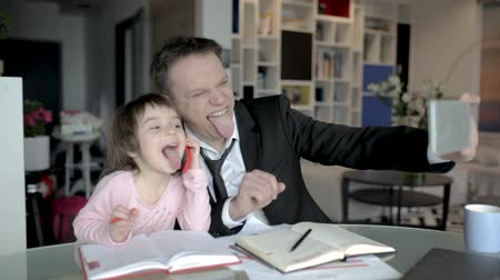 söylemek : Lovely Father And Daughter Take Selfie Showing Tongues. Man In Suit And Little Child Wave And Say Hi To The Camera Of A Phone. Stok Video