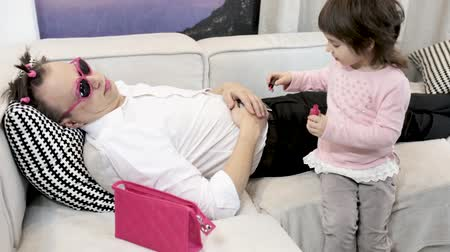 bok : Concentrated Girl Paints Fingernails Of Her Sleeping Father With Pink Colour. Cute Daughter Pains Her Fathers Nails