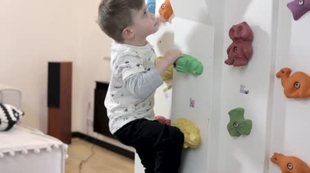 wspinaczka : Brave Active Boy Trains On A Climbing Wall At Home. Handsome Boy Climbs A Rock Wall Playing