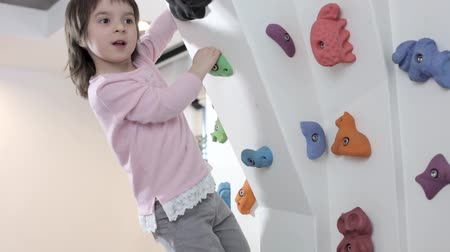 szórakoztatás : Charming Girl Has Fun On The Climbing Wall. Smiling Child Climbs A Rock Wall In The Playing Centre.
