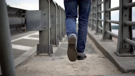 tcheco : Young Man Wearing Jeans And Boots Walking On Bridge. Selective Focus On Legs. Man Alone Concept.