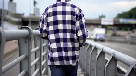 cumhuriyet : Back View ge OF Young Man wearing Jeans Walking On Bridge. Selective Focus On Legs.