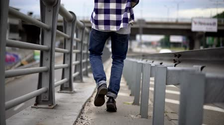 tcheco : Young Man In Blue Jeans And Black Boots Walking On Stone Bridge. Solo Walking Concept. Stock Footage