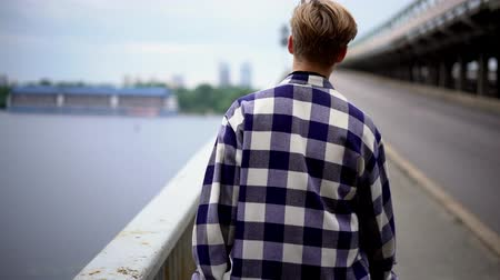 tcheco : Sexy Blonde Man In Checkered Shirt Walking On Wide Stone City Bridge. Man Alone Concept.